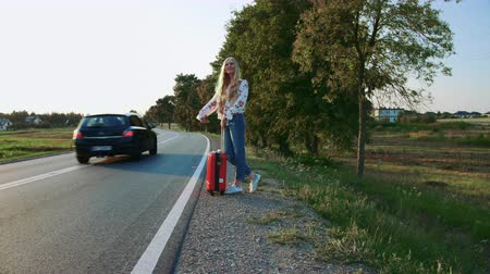 országúti : Traveler woman hitchhiking on a sunny road and walking.