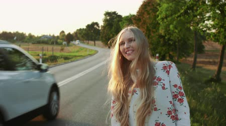 yol kenarı : Traveler woman hitchhiking on a sunny road and walking. Slow motion. Stok Video
