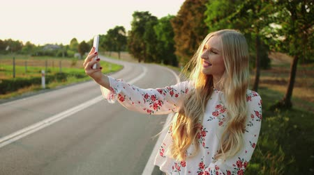 viagem por estrada : Woman making video call near countryside road. Young lady smiling and using modern smartphone to make video call while hitchhiking in Europe countryside.