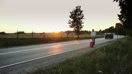 abaixo : Young woman hitchhiking on countryside road. Vídeos