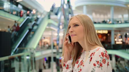 turysta : Young woman speaking on phone in mall. Wideo