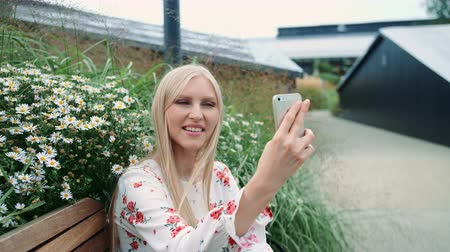 ławka : Lovely young Woman using smartphone to make video call while sitting on bench on living roof of huge mall Wideo