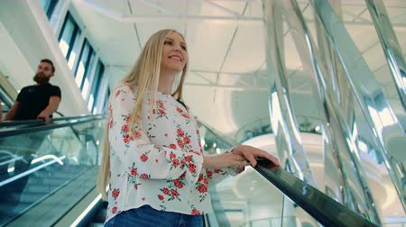 ライディング : Woman riding escalator in mall. From below shot of lovely young lady looking up while riding moving staircase in modern mall in Europe.