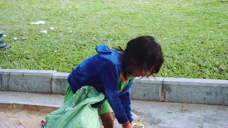 Камбоджа : A Little girl Throws Garbage In The Trash In In The Capital Of Cambodia Phnom Penh
