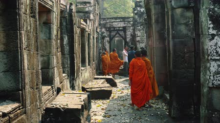 Ангкор : Young Buddhist Monks Walking In Temple In Saffron Robes and Looking Out Over Angkor Wat. Стоковые видеозаписи
