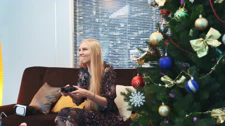 ona : Side view of excited lady winning a video game on console on Christmas. She sits near the Christmas tree in the living room with skyscrapers in the background. There are also VR glasses headset on sofa. Dostupné videozáznamy