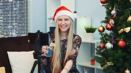 şerefe : Close up of gorgeous young lady in Santa hat shooting a video blog by smartphone at home. She has a drink in her hands and a Christmas tree on the right.