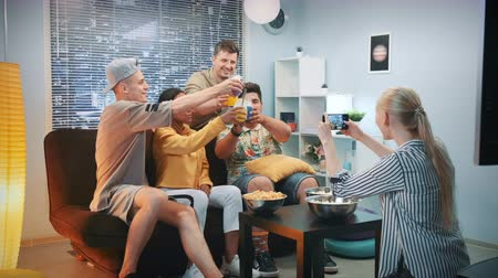 em casa : Woman making photo of friends sitting on sofa with cocktails by smartphone. The group of people cheers, having fun and posing on camera.