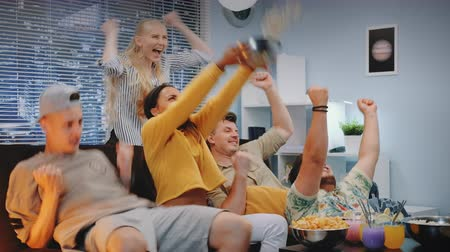 есть : Girls and boys watching sports on TV and spilling popcorn when team scores. They are screaming happily, jumping and raising clenched fists. There are skyscrapers in the background.