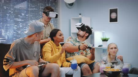 konsola : Two young men playing online game in virtual reality glasses, one guy wins the battle. Their friends cheer up them, eating snacks and drinking dry ice cocktails.