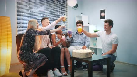 Multi-ethnic young people making toasts with dry uce cocktails on birthday party. There is a big birthday cake with candles on table. Elements of this image furnished by NASA.