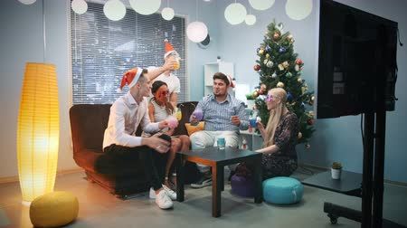 Young people in Santa hats and party masks making cheers on Christmas. They celebrate holiday at home near the Christmas tree. Stok Video