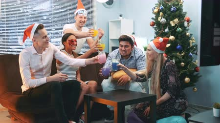 Happy New Years celebration in cheerful company in Santa hats nd party masks making toasts to each other sitting near the Christmas tree