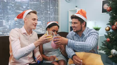 Close up of two boys and a girl in Santa hats making cheers and blowing party whistles. They have fun celebrating holidays together. Elements of this image furnished by NASA.