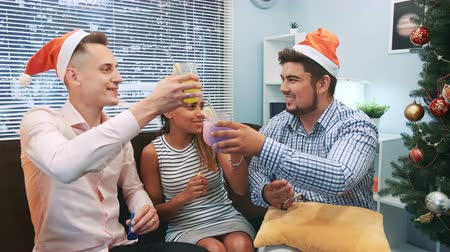 cheers : Close up of three friends in Santa hats making cheers and blowing party whistles. They have fun celebrating holidays together. Elements of this image furnished by NASA.