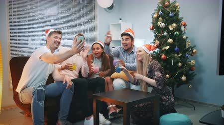 apito : Cheerful friends in Santa hats making video call by smartphone on Christmas party while blowing party whistle, making cheers and having fun together.