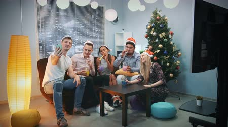 Young mixed race people in Santa hats making video call by smartphone on Christmas party while blowing party whistle, making cheers and having fun together. Stok Video