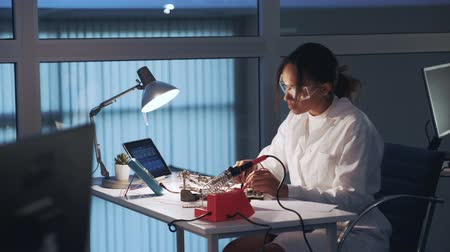 African american electronics specialist making tests on motherboard with multimeter tester in lab. Woman working in white coat and protective glasses