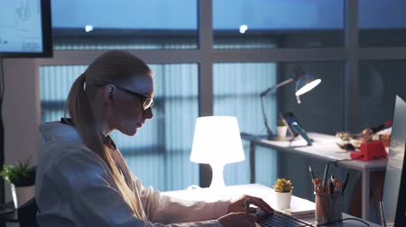 Side view of professional electronics specialist working on the computer in modern laboratory. Woman is in white coat and glasses
