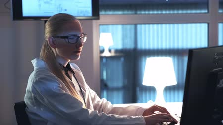 Female electronics engineer working on the computer and writing the results of the research in laboratory. Woman is in white coat and glasses