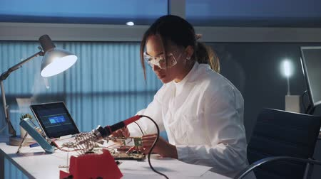 Side view of african american electronics specialist working with multimeter tester, and other electronic devices in laboratory sitting at the table in protective glasses and white robe. Stok Video
