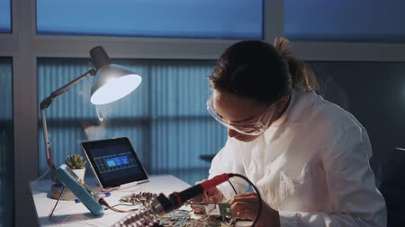 Close up of female engineer of electronics in white coat and protective glasses checking motherboard with multimeter tester and other electronic devises Stok Video