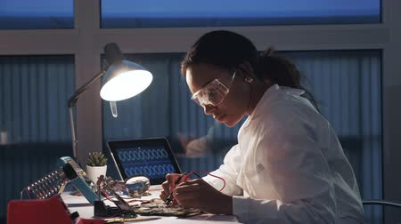 Side view of female electronics engineer working with multimeter tester and other electronic devices in laboratory