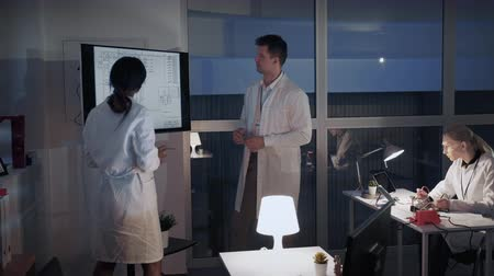 multiethnic : Chief engineer explaining details of investigation to his colleague in laboratory by showing on big TV screen