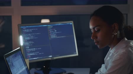 Close up of african american woman working on computer in electronics laboratory. Doing Development of Software and Hardware. She wearing a lab coat. Side view