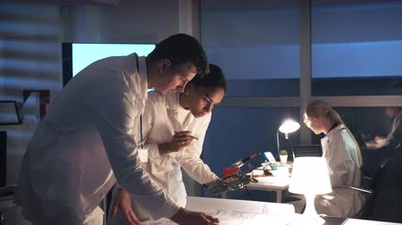 Technology Research Laboratory: Mixed race electronics engineers in white coats working with motherboard and control electronics scheme in lab. They discussing many questions Stok Video