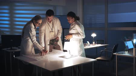 Technology Research Facility: Multiracial Electronics Development Engineers in white coats working in lab with motherboard and control electronics scheme. They discussing and analyzing details