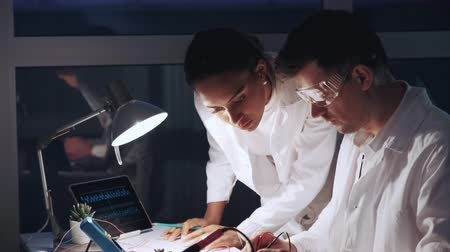 Close up of african american woman and man in protective glasses working in modern electronics laboratory. They using multimeter tester and other electronic devices.