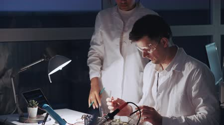 Two mixed race electronics engineers working with multimeter tester and other electronic devices. Man is in protective glasses. Stok Video