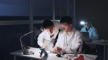 Mixed race electronics engineers in white coats working on motherboard using multimeter tester. Man is in protective glasses