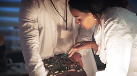 Close up of african american woman in lab coat discussing motherboard building with other engineers. Multiracial team work. Stok Video
