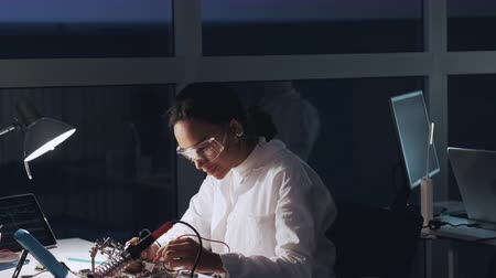 Middle close up of african american engineer making tests on motherboard in lab. She is protective glasses. Scientist working in a laboratory with happy emotion.