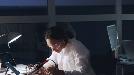 African american electronics specialist in protective glasses and white coat working with multimeter tester and motherboard in lab aquipped with other electronic devices. Scientist working in a laboratory with happy emotion. Stok Video