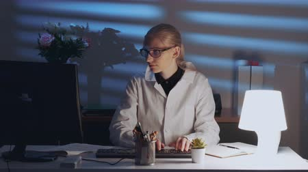 Smart female engineer working on computer and enjoying success in work. She is in lab coat and with glasses Stok Video