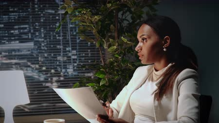 açıklayan : Beautiful african american business woman explaining the text of contract in office. There are skyscrapers in the background. Stok Video