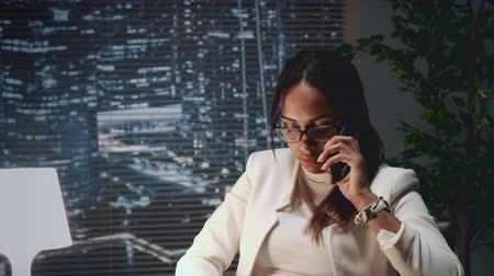 clienten : Close up of multiracial business lady speaking by smartphone with a client at her office. She is in black eyeglasses.