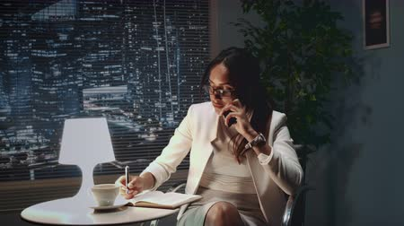 African american business woman in eyeglasses speaking by smartphone with something at her office. There are skyscrapers in the background. Stok Video