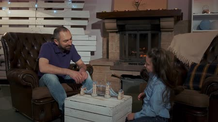 kleine meisjes : Family evening time: father and daughter learning 3D model of bridge sitting near the fireplace at home