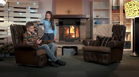 привлекать : The brother doesnt want to play with his younger sister with plane, so the girl is upset. In the background - fireplace.