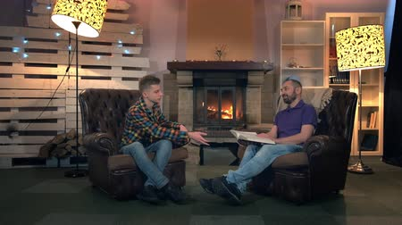otcovství : Father and son speaking about the greatest book of all times sitting on leather armchairs near the fireplace at home