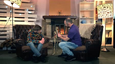 szkielet : Father explaining his elder son the bone structure of human body showing on skeleton. They sitting on comfortable armchairs near the fireplace
