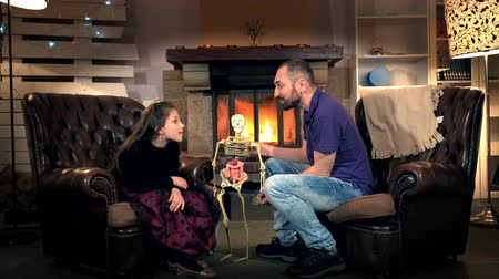 peça : Little daughter giving father interesting questions about the human body structure. Dad holding in his hand human sceleton. In the background - fireplace.