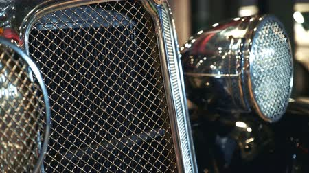 kaloryfer : Close-up of shiny chrome radiator grill of old vehicle. There are also two big headlights in shot