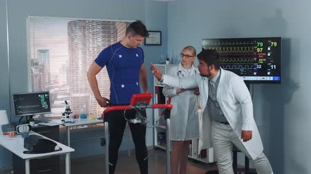 teste : Sports Laboratory: Mixed race doctors of sport lab discussing EKG of treadmill test displayed on a big TV screen while the athlete standing on racetrack
