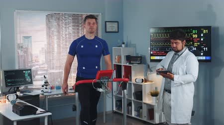 závodní dráha : Multiracial sport professional performing stress test while the athlete walking on treadmill. Computer supervises whole test process. In Scientific Sports Laboratory.
