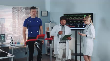 심장학 : Diverse cardiology technologists speaking about athlete fitness level during the stress test on racetrack. Physical parameters of his body are shown on two displays.